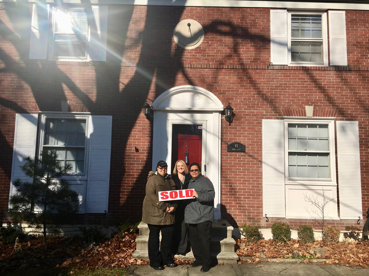 "Happy Couple Holding a ""SOLD"" Sign Celebrate in front of their new home"