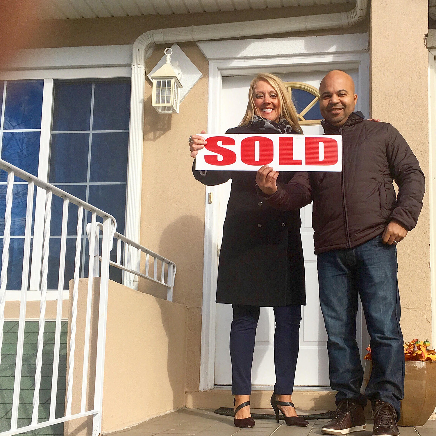 "Holly poses with a happy client while holding an over-sized ""Sold"" sign"