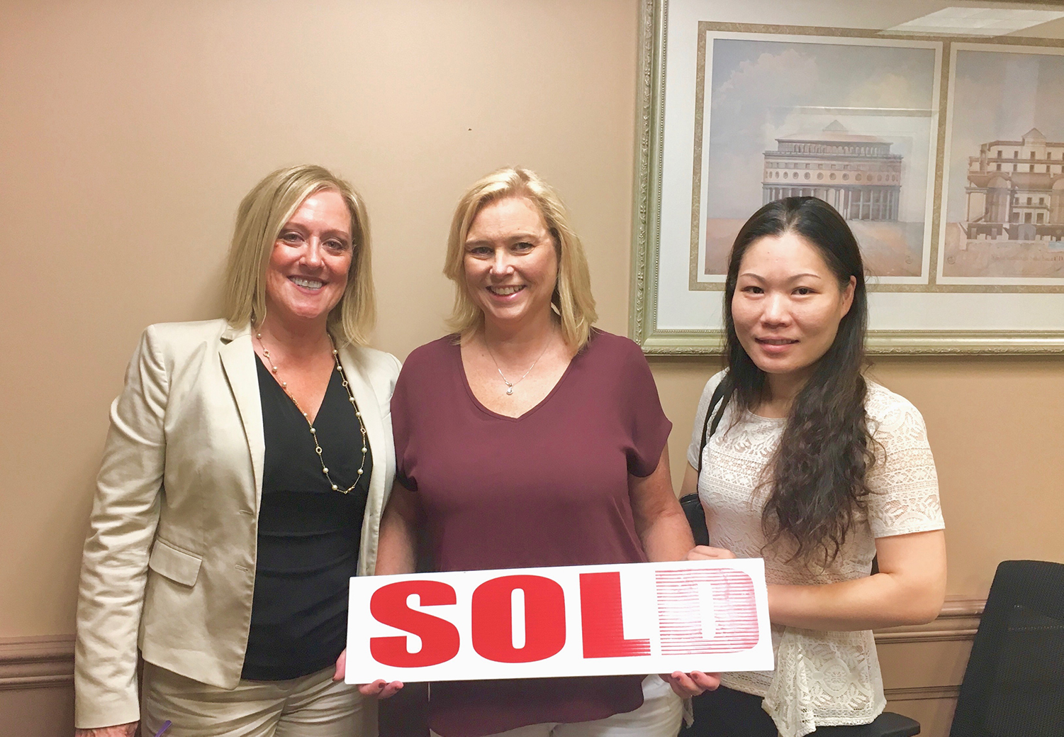"Photo of Happy Client, Rosemary, holding up a ""sold"" sign"