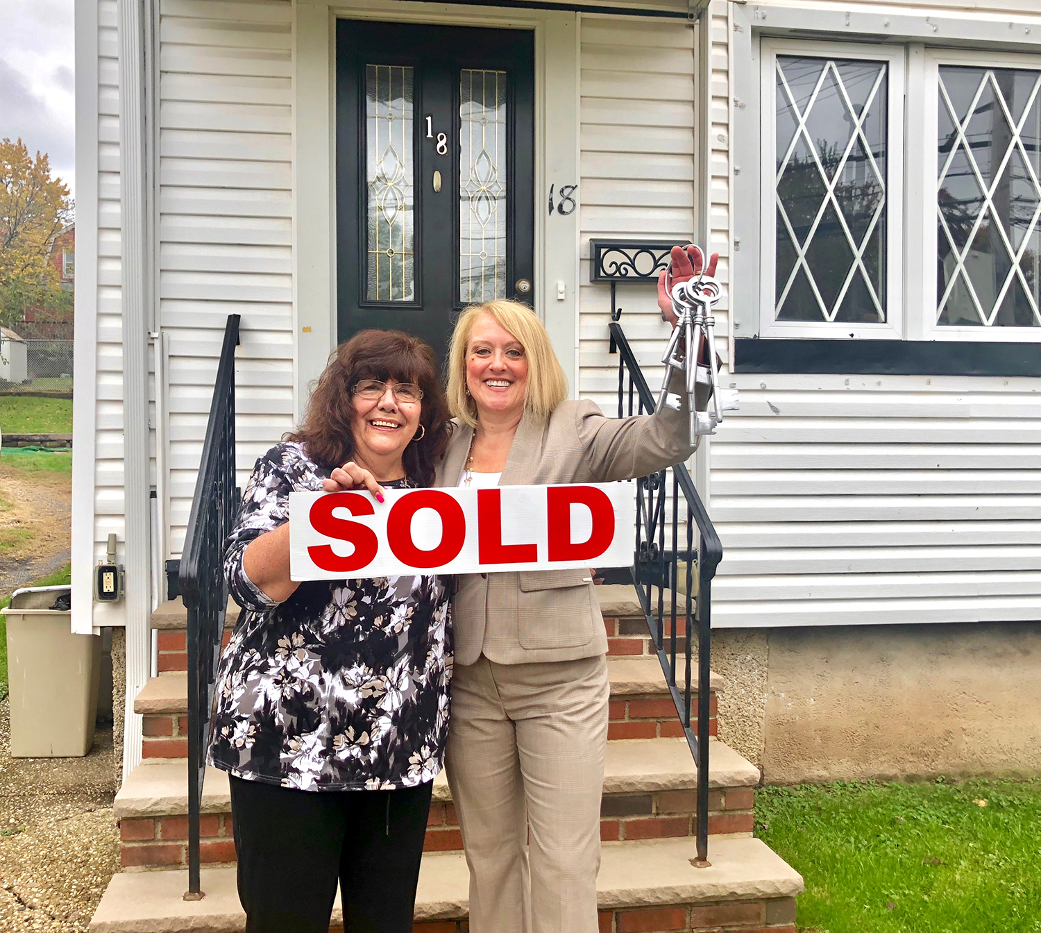 Happy Client Libby in front of her new home with Holly Wiesner Olivieri